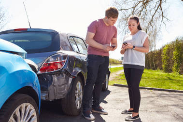 two-young-drivers-exchanging-details-due-to-a-small-car-accident
