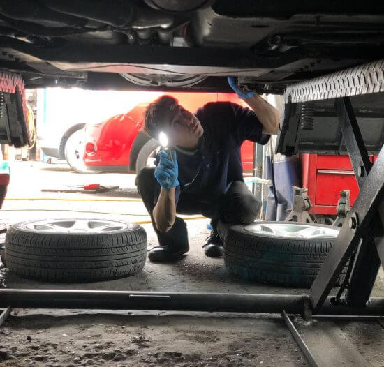 mechanic-looking-under-car